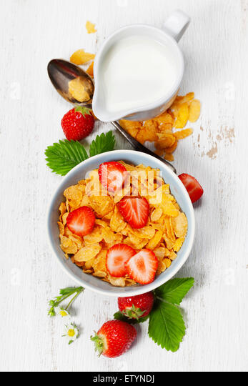 Healthy Breakfast with corn flakes, milk and strawberry on old wooden background. Health and diet concept - Stock-Bilder