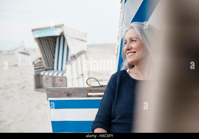 Smiling senior woman looking away on beach - Stock Image