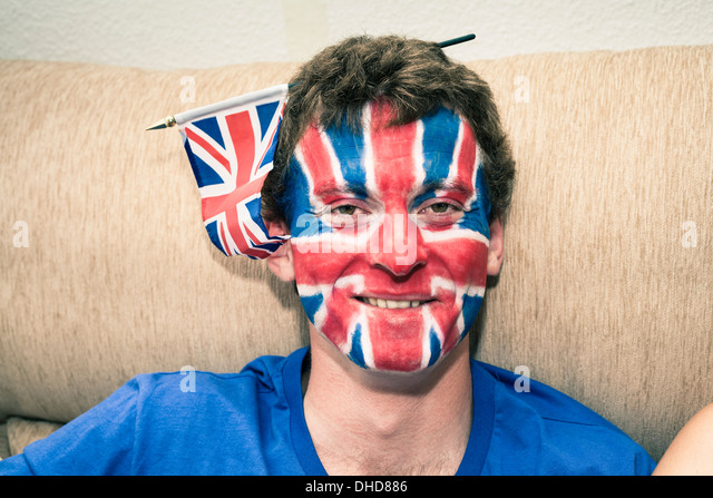 Portrait of funny man with British flag painted on his face. - Stock Image