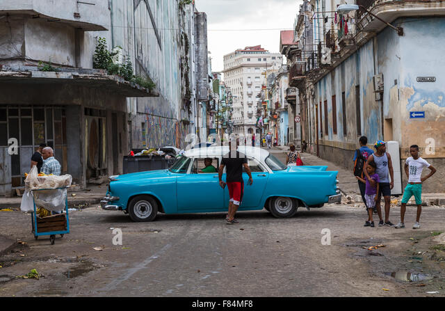 Looking over Calle Consulado in Cento Havana, Cuba as a classical car passes some locals on the streets. - Stock Image