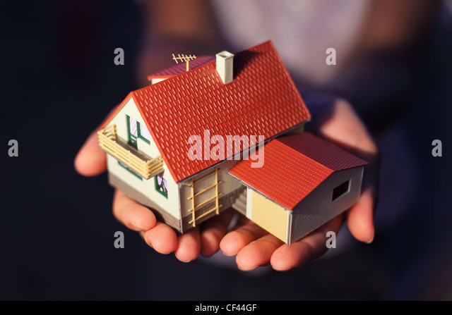 model of house with garage on hands - Stock Image