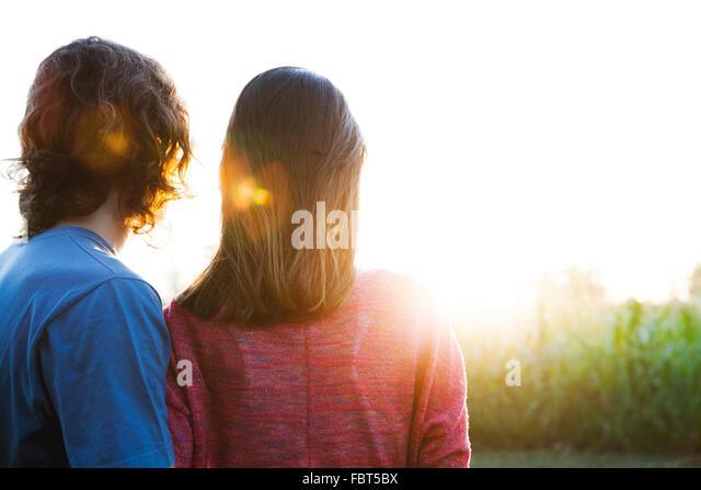 Young couple watching sunset - Stock-Bilder