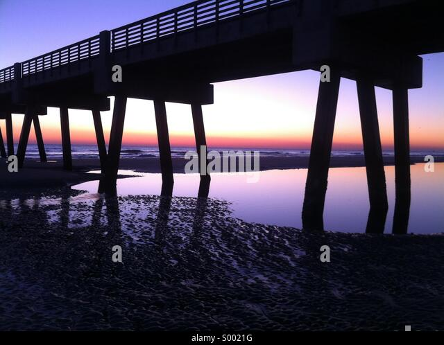 Pooled water reflects a vibrant sunrise sky at Jacksonville Beach Pier in Jacksonville Beach, Florida. USA. - Stock Image