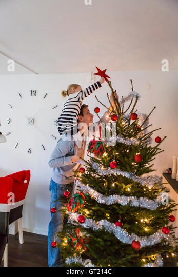 Father and daughter decorating Christmas tree at home - Stock-Bilder