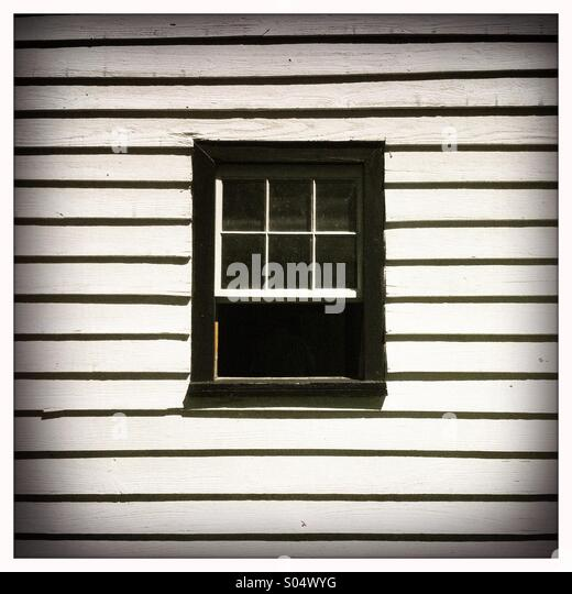 A black framed house window on a white wooden wall - Stock Image