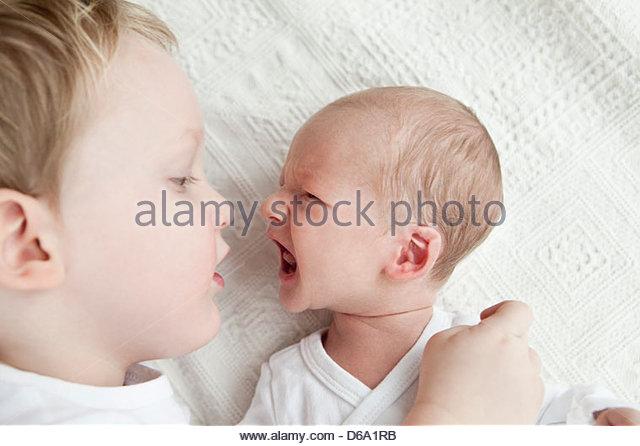 Infant boy crying at older brother - Stock-Bilder