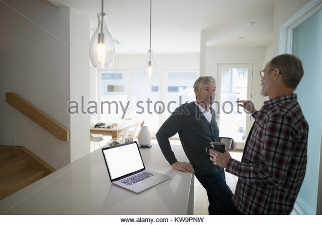 Senior male gay couple talking and drinking coffee near laptop in kitchen - Stock Image