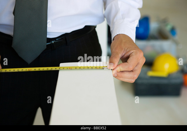 Well-dressed person measuring ledge width, close-up - Stock Image