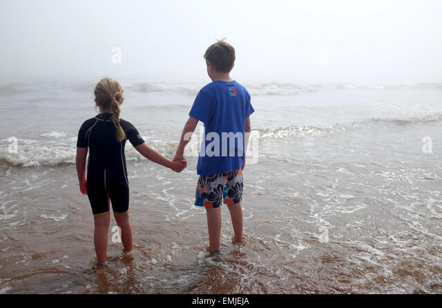 A young boy and girl holding hands look out to the sea on a misty day - Stock Image