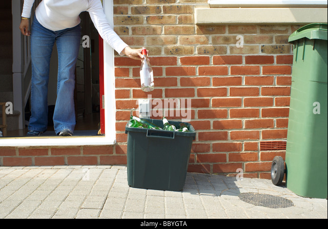 Woman putting out the recycling - Stock Image