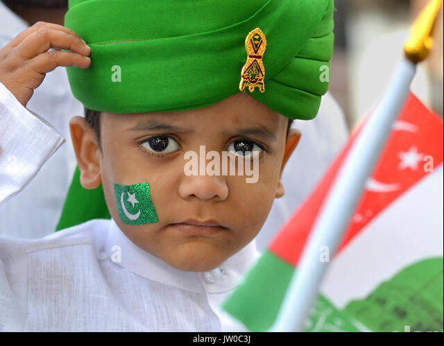 Little Indian Muslim boy, wearing a green turban and saluting during Rabi' al-awwal festivities (Muhammad's - Stock Image