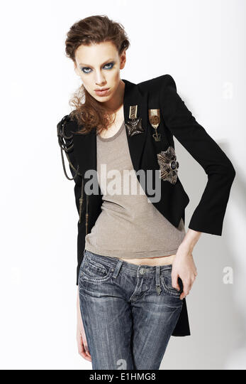 Individuality. Beautiful Eccentric Fashion Model in Jeans and Bijou on Jacket - Stock Image
