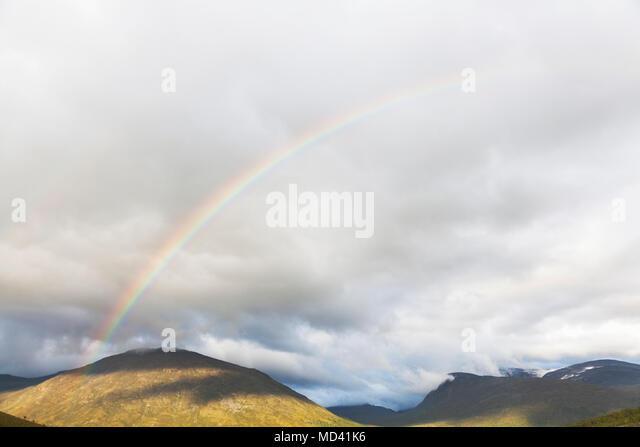 Rainbow over mountain landscape, Jotunheimen National Park, Lom, Oppland, Norway - Stock Image