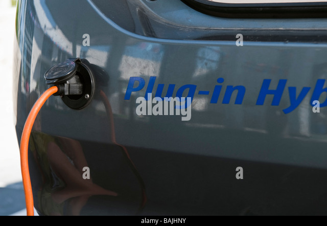 Close up of electrical plug recharging electric car - Stock Image