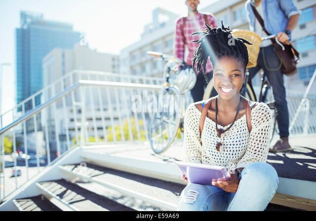 Woman using digital tablet on city street - Stock Image