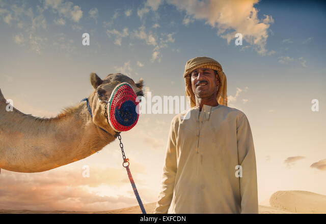 Portrait of camel and bedouin in desert, Dubai, United Arab Emirates - Stock Image