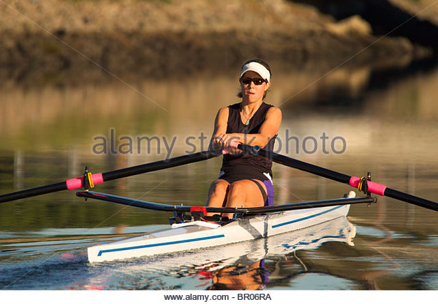 A woman rower during a morning workout - Stock Image