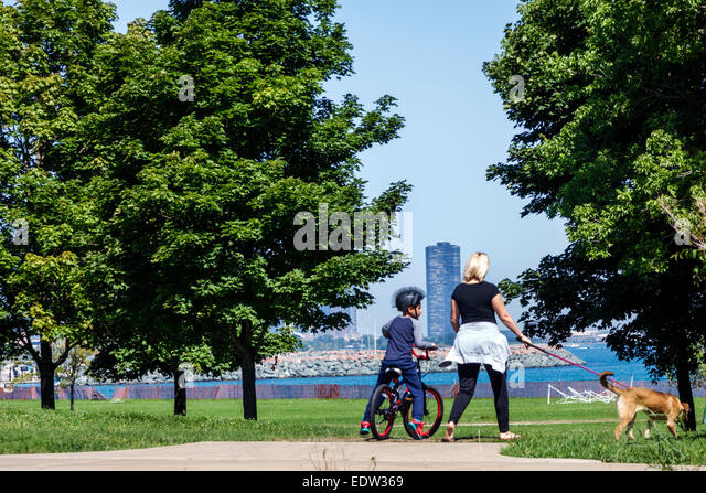 Illinois Chicago Lake Michigan South Side 39th Street Beach Lakefront Trail water trees biker riding bicycle rider - Stock Image