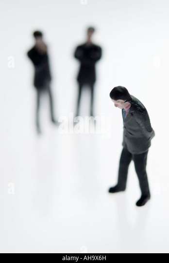 Downcast man watched by figures in the background - Stock Image