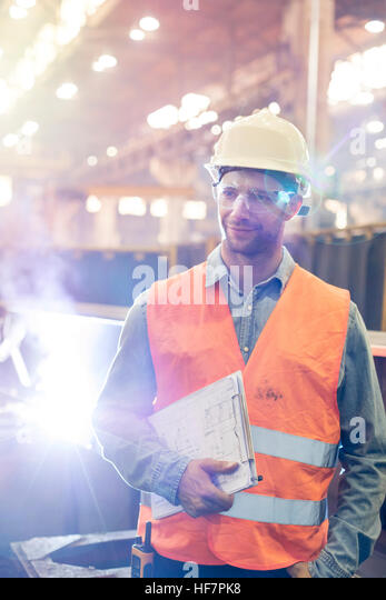 Steel worker with clipboard in factory - Stock Image