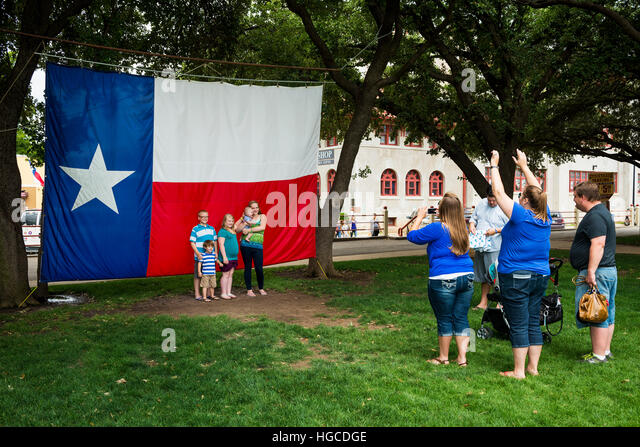 Fort Worth, Texas, USA - June 10, 2014: Family taking a photo in front of the Texas Flag in the Fort Worth Stockyards, - Stock-Bilder