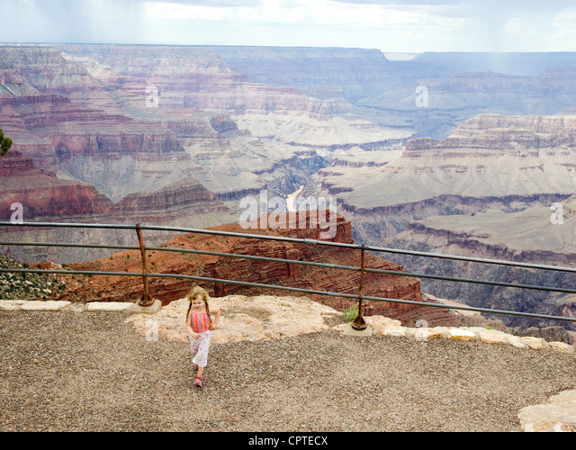 Girl walking away from canyon edge - Stock Image