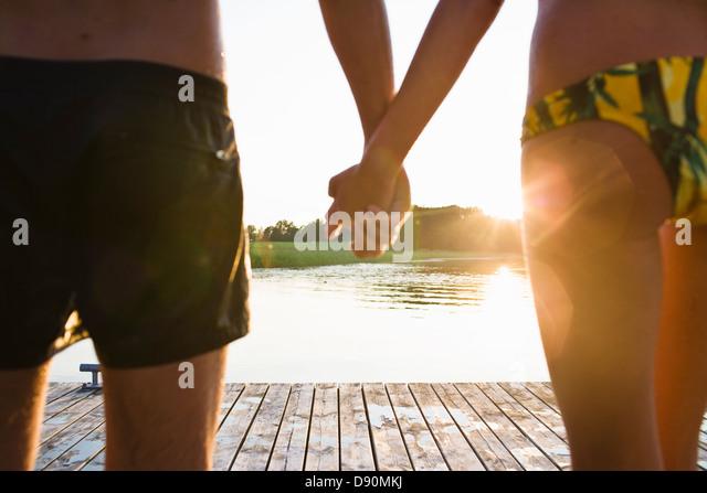 Couple holding hands on jetty - Stock-Bilder