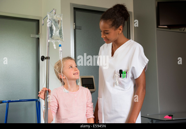 Female nurse assisting to a girl patient in hospital - Stock Image