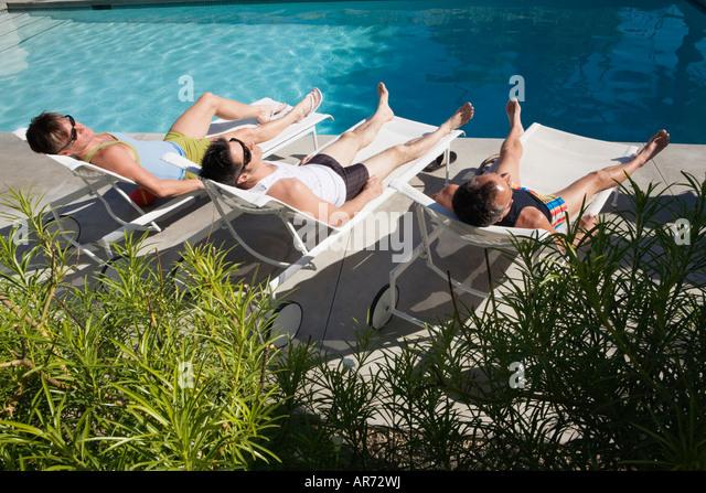 Men relaxing in lawn chairs beside swimming pool - Stock-Bilder