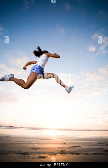 A woman runs in athletic gear in Oceanside, California. - Stock Image