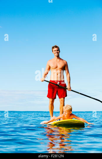 Father and Son Stand Up Paddling. Having Fun Outdoors. Summer Lifestyle. - Stock Image