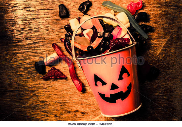 Eerie holiday background on a halloween pumpkin can tipped over in all you can eat view from above. Sugar high - Stock Image