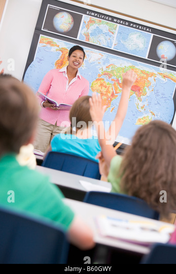 Students in geography class volunteering for teacher (selective focus) - Stock Image