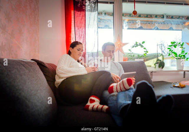 Couple using tablet and smart phone while relaxing on sofa at home - Stock-Bilder