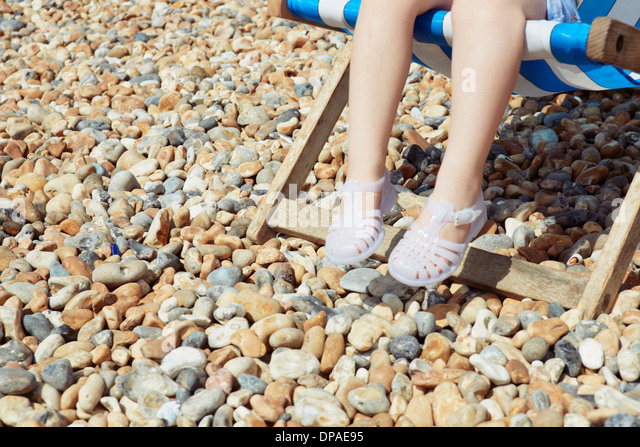 Child with plastic sandals on beach deck chair - Stock Image