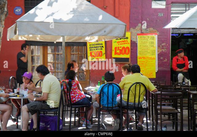 Santiago Chile Bellavista Pio Nono sidewalk cafe restaurant dining table umbrella menu Spanish special Hispanic - Stock Image