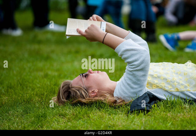 Hay on Wye, Wales, UK Saturday 28 May 2016Pictured: A young woman reads a book on the festival greenRe: The 2016 - Stock Image