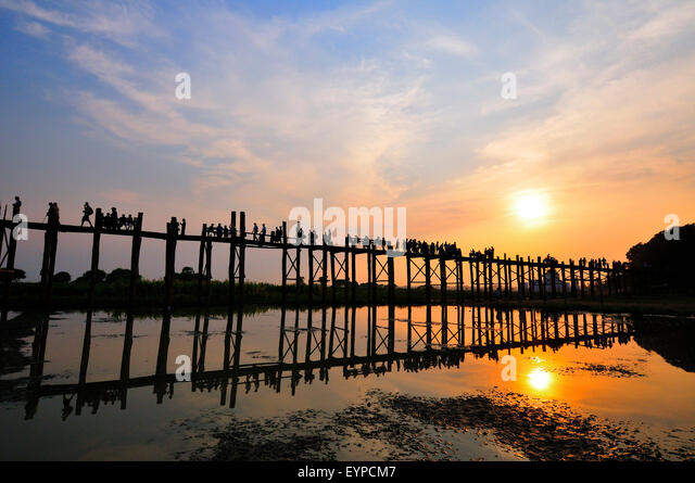 Silhouettes of tourists who come at sunset to walk along  the famous 1.2 kms  long U Bein Teak Bridge Amarapura, - Stock-Bilder