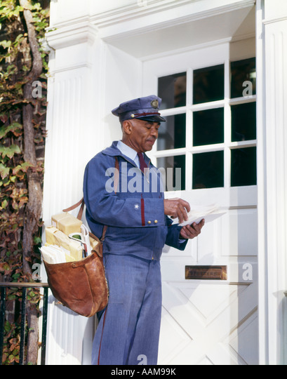 1960s AFRICAN-AMERICAN MAN MAILMAN RETRO CARRYING MAILBAG SORTING LETTERS FRONT DOOR DELIVERY DELIVERING USPS - Stock Image