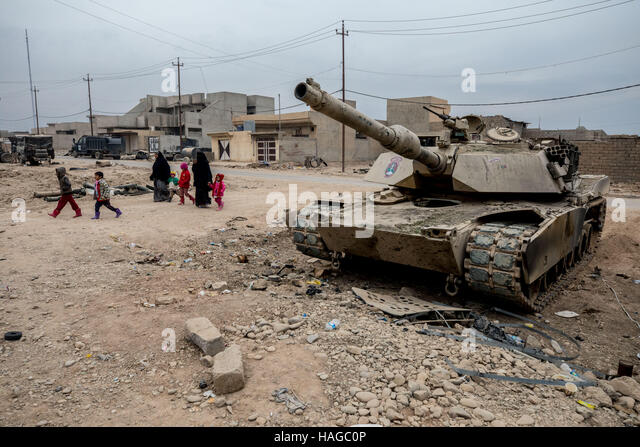 Mosul, Ninewa Province, Iraq. 30th Nov, 2016. A family walks past a destroyed M-1 Abrhams tank in Gogjali. Credit: - Stock Image