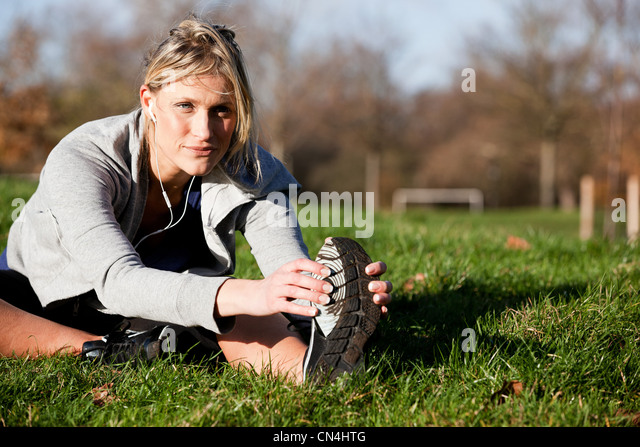 Mid adult woman performing warm-up exercises in park - Stock Image