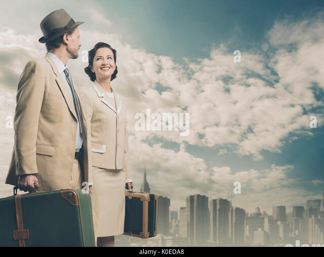 Elegant vintage couple holding suitcases with skyline on background, travel concept - Stock Image
