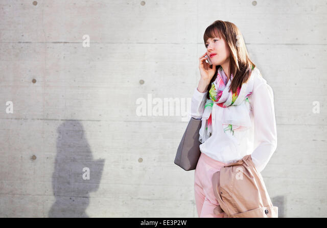 Young woman using phone outdoors, Munich, Bavaria, Germany - Stock-Bilder
