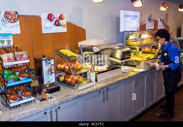 Silver Spring Maryland Holiday Inn Express hotel free breakfast buffet cereal fruit Asian woman attendant interior - Stock Image