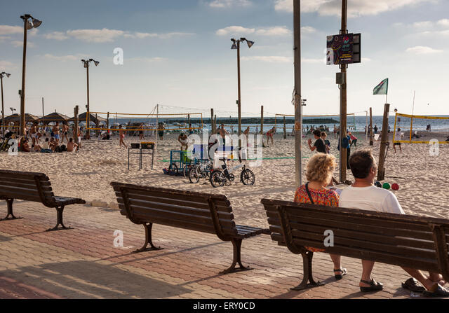 people sitting along Tel Aviv seafront , Israel - Stock Image