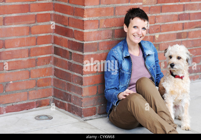 Woman and dog sitting on city street - Stock Image