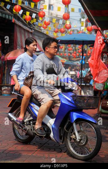 Bangkok Thailand Samphanthawong Chinatown Mangkon shopping market marketplace Asian man woman couple motorcycle - Stock Image