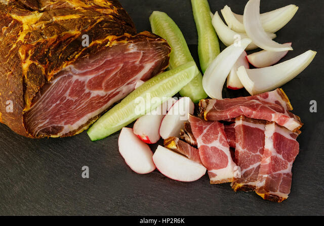 smoked pork bacon with vegetables and herbs on a kitchen dark wooden table - Stock Image
