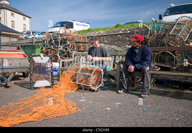 Fishermen mending nets on the harbourside at Eyemouth - Stock Image