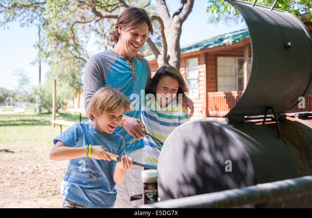 USA, Texas, Father with two sons having fun at barbecue - Stock Image